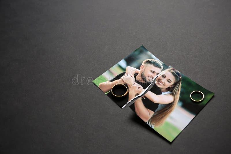 Poszarpana fotografia szczęśliwa para z pierścionkami na ciemnym tle Poj?cie rozw?d zdjęcie stock