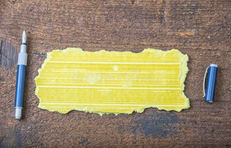 Poszarpany kawałek stary papier dla wiadomości lub słowa mądrość z piórem na brown drewnie zdjęcia royalty free