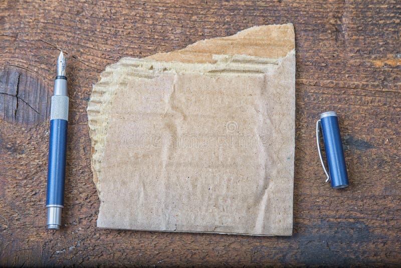 Poszarpany kawałek stary papier dla wiadomości lub słowa mądrość z piórem na brown drewnie fotografia royalty free