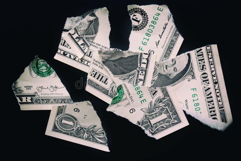 Poszarpany rozdzierający devalued jeden dolarowy banknot na czarnym tle obraz stock
