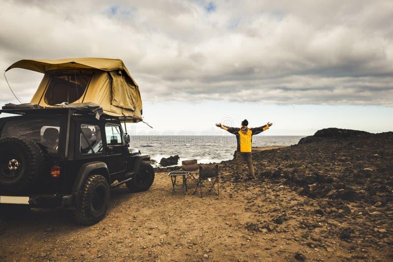 Poszukiwacz przygód mężczyzna w podróży podróży z z drogowym samochodu, dachu namiotem cieszyć się i odkrywa światowego utrzymani zdjęcia stock