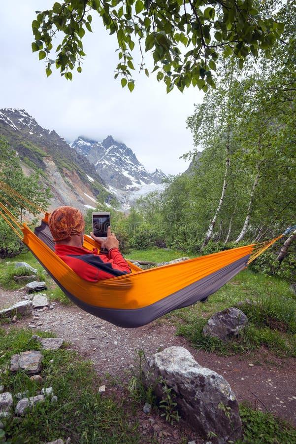 Poszukiwacz przygód relaksuje w hamaku w górach, bierze fotografię u zdjęcie royalty free