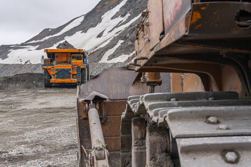 Potężny łupu buldożeru i gigat usypu ciężarówki działanie w apatycie minuje w Murmansk regionie zdjęcie stock
