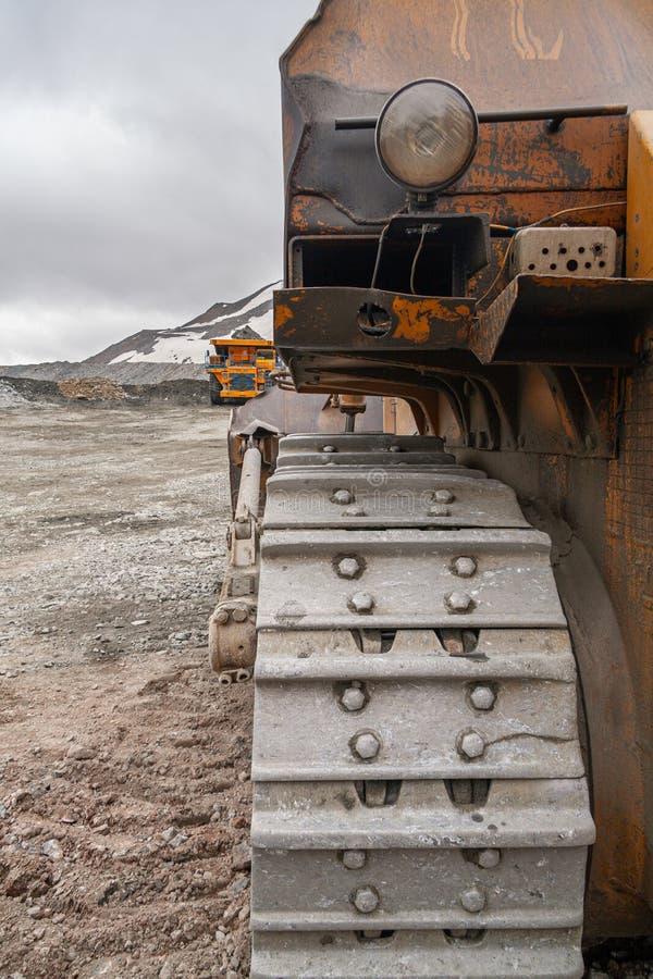 Potężny łupu buldożeru i gigat usypu ciężarówki działanie w apatycie minuje w Murmansk regionie obrazy royalty free