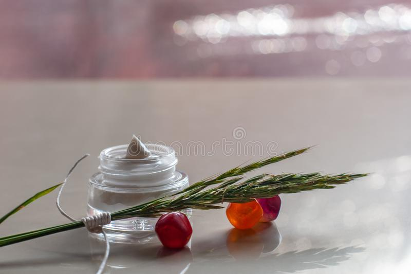 Pot avec de la crème et les épillets blancs sur les cailloux en verre colorés photo libre de droits