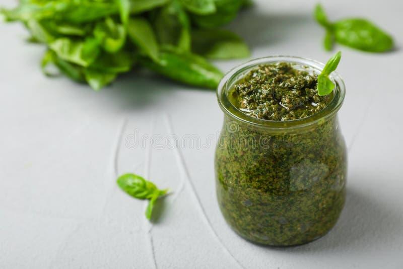 Pot avec de la sauce à pesto de basilic sur la table images stock
