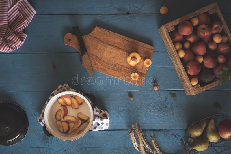 Pot avec des tranches et des fruits frais de pêche dans la boîte fabrication de confiture photographie stock libre de droits