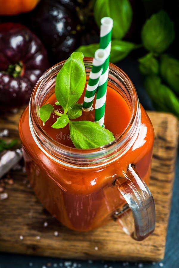 Pot avec le jus de tomates fait maison frais photo stock
