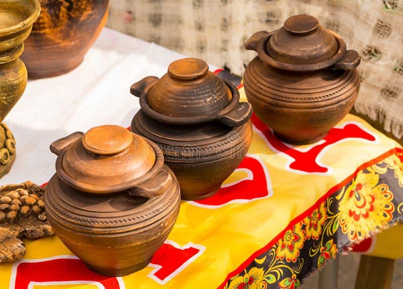 POT beventi asiatici Tre navi con un coperchio stanno in una fila, un fondo rustico immagini stock libere da diritti