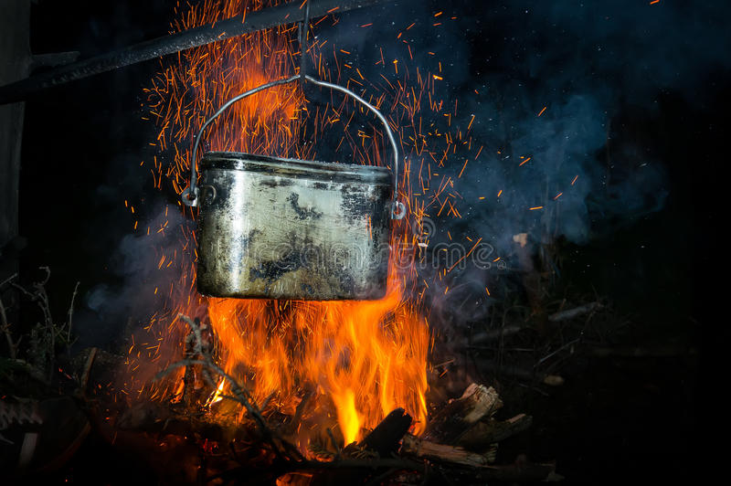 A pot of boiling water on the fire in the forest. Cooking without electricity is a Concept of natural tourist romance away from civilization royalty free stock photo
