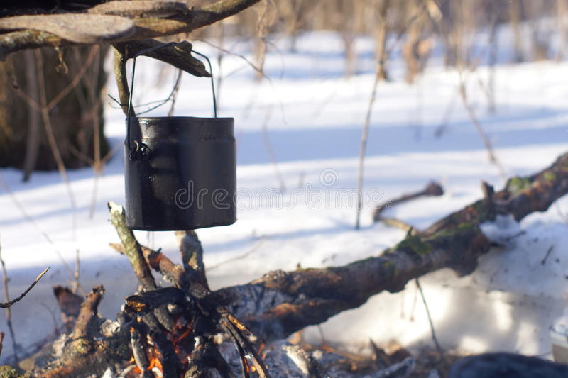 A pot of boiling water on the fire warms in the winter forest, stock photography