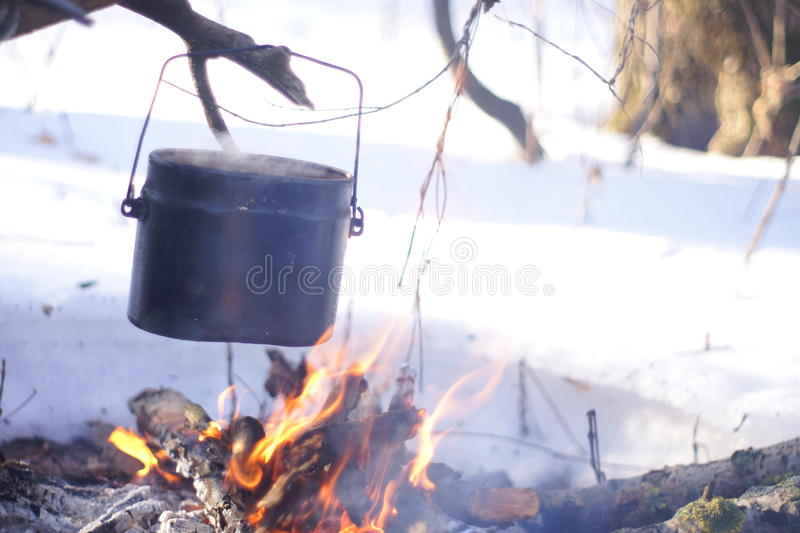 A pot of boiling water on the fire warms in the winter forest, royalty free stock photos
