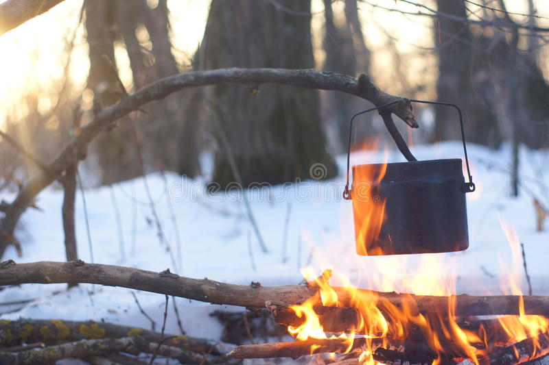 A pot of boiling water on the fire warms in the winter forest, stock images