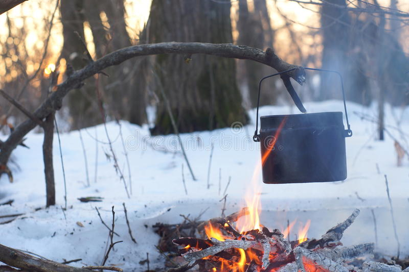 A pot of boiling water on the fire warms in the winter forest, royalty free stock images