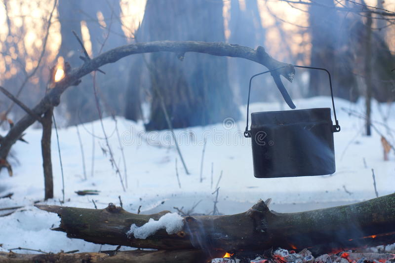A pot of boiling water on the fire warms in the winter forest, stock image