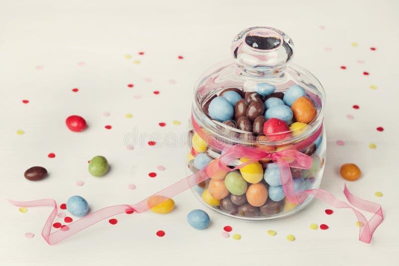 Pot coloré de sucrerie décoré du ruban d'arc sur le fond blanc avec des confettis photographie stock