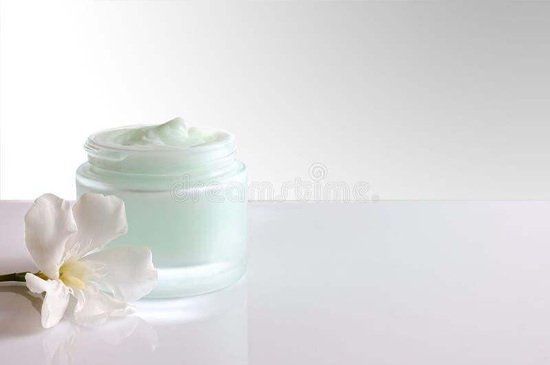 Pot crème ouvert avec le blanc de vue de face de fleur photo stock