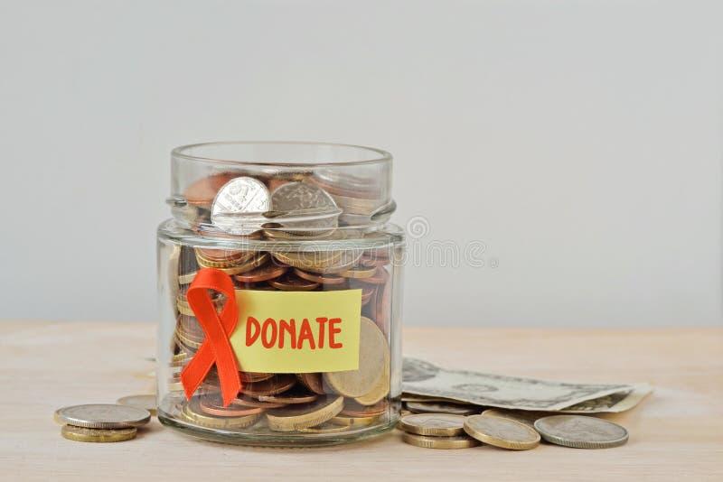 Pot d'argent complètement de pièces de monnaie avec le ruban orange et donner le label - concept de leucémie, de cancer de rein,  photo stock