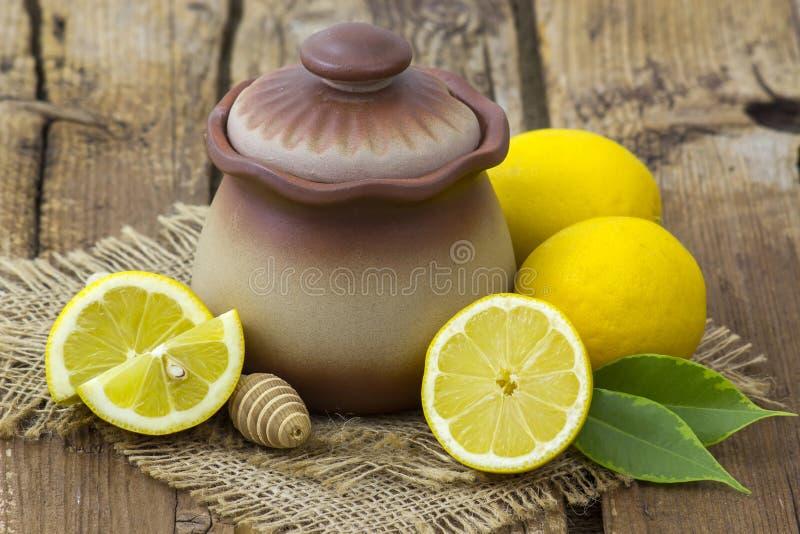 Pot d'argile avec du miel et les citrons frais images libres de droits