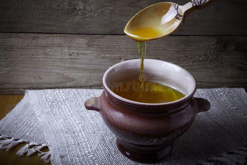 Pot d'argile avec le ghee et la cuillère sur la serviette de toile Toujours durée rustique image stock