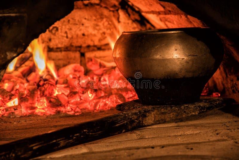 Pot dans le four et une pelle en bois image libre de droits