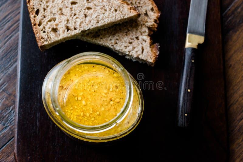 Pot de beurre d'arachide avec des tranches de pain et de couteau sur le conseil en bois photo stock