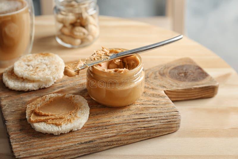 Pot de beurre d'arachide crémeux avec du pain photo stock