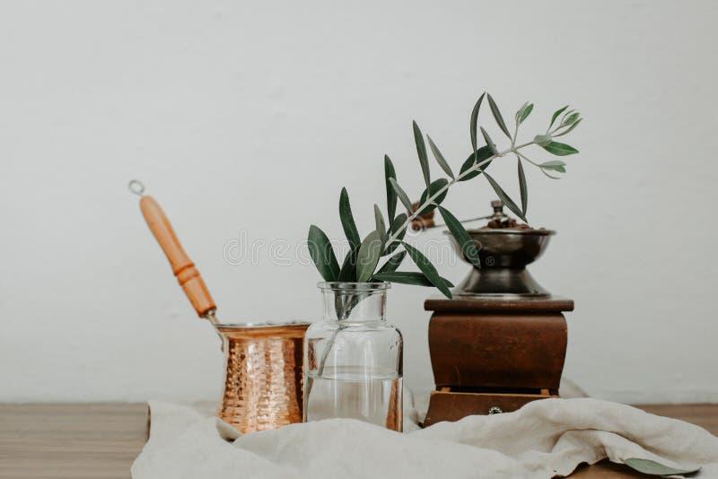 Pot de café de tonnelier, vase avec la branche d'olivier et vieux moulin à café image libre de droits