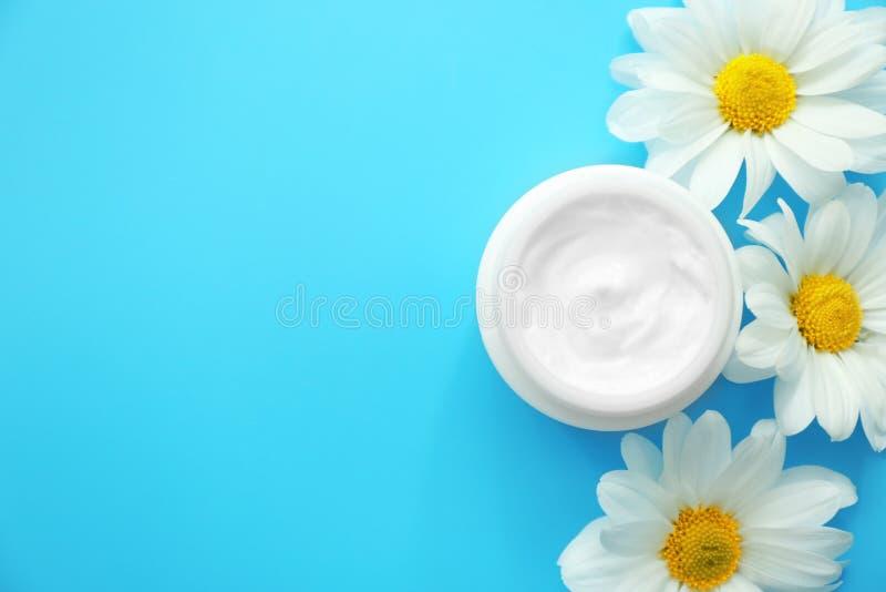 Pot de crème avec l'extrait et les fleurs de fines herbes sur le fond de couleur images libres de droits
