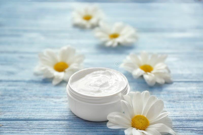 Pot de crème avec les fleurs de fines herbes d'extrait et de marguerite sur le fond en bois blanc images stock