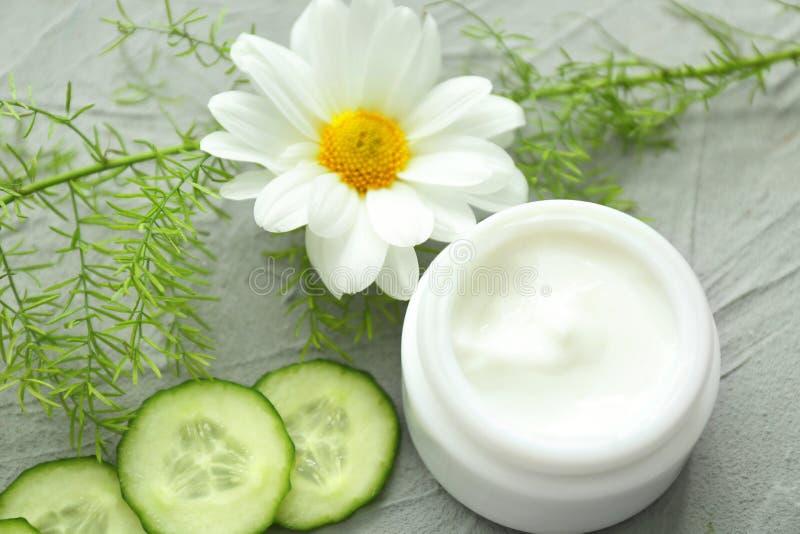 Pot de crème avec les tranches de fines herbes d'extrait et de concombre sur le fond gris photographie stock