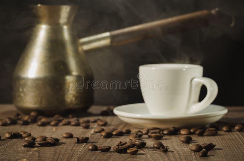 Pot de cuivre et tasse de café chaude/pot de cuivre et tasse de café chaude sur une table en bois avec le fond foncé Foyer sélect image libre de droits