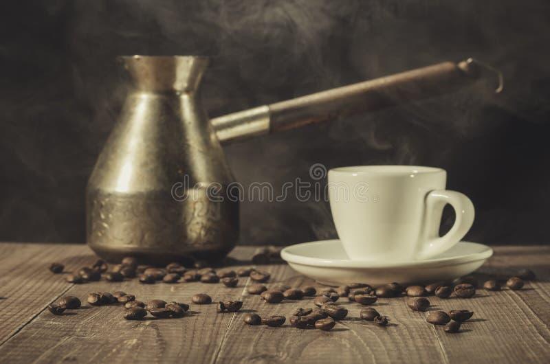Pot de cuivre, tasse et grains de caf? chauds/pot de cuivre, tasse chaude et grains de caf? sur une table en bois avec le fond fo image libre de droits