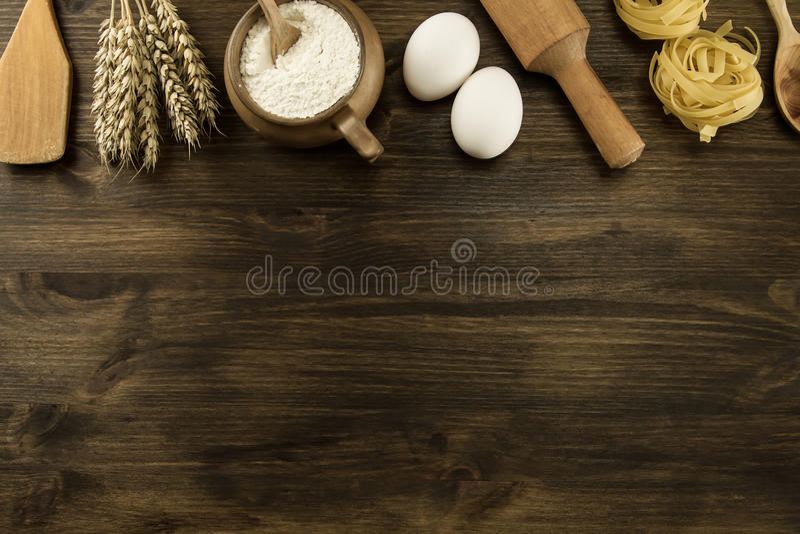 Pot de farine, oreilles de blé, pâtes, ustensiles de cuisine sur le fond en bois fait maison, menu, recette, moquerie  photographie stock