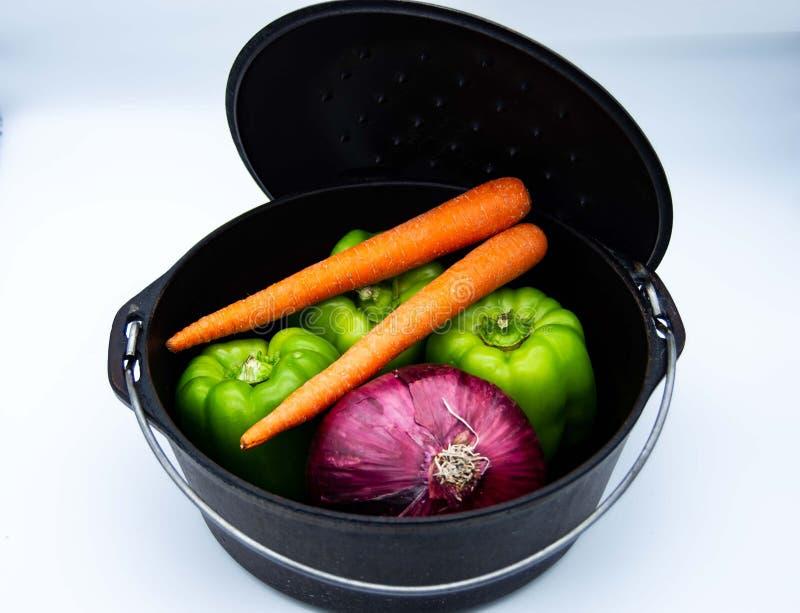 Pot de fonte avec des légumes image libre de droits