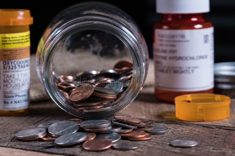 Pot de maçon en verre avec quelques pièces de monnaie à l'intérieur avec des médicaments délivrés sur ordonnance photographie stock