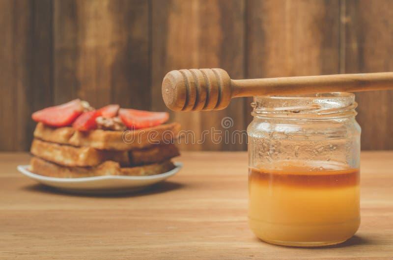 Pot de miel avec le plongeur de miel et les gaufrettes faites maison décorées de la fraise et de la noix sur un fond en bois s?le photos stock