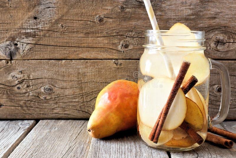 Pot de poire, gingembre, l'eau de detox de cannelle contre le bois rustique photographie stock