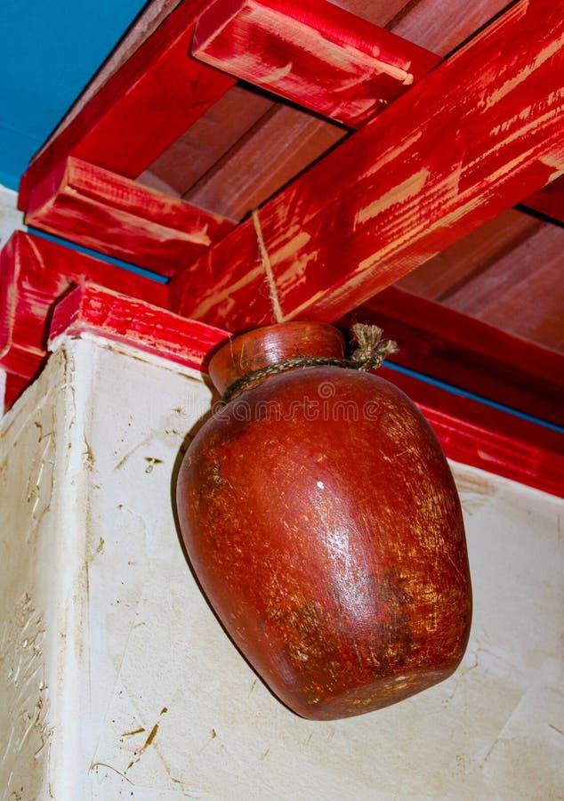 Pot de poterie de terre accrochant par la corde des combles rouges contre le mur blanc de stuc image stock