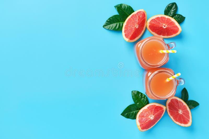 Pot deux de jus de pamplemousse frais sur un fond bleu Vue supérieure photographie stock
