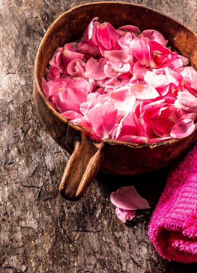 Pot en bois de pétales de rose photographie stock