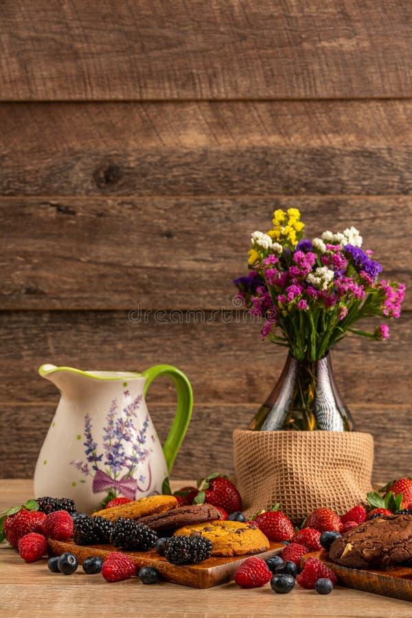 Pot en céramique, vase en verre avec des fleurs et biscuits assortis avec le mélange des baies sauvages photographie stock libre de droits