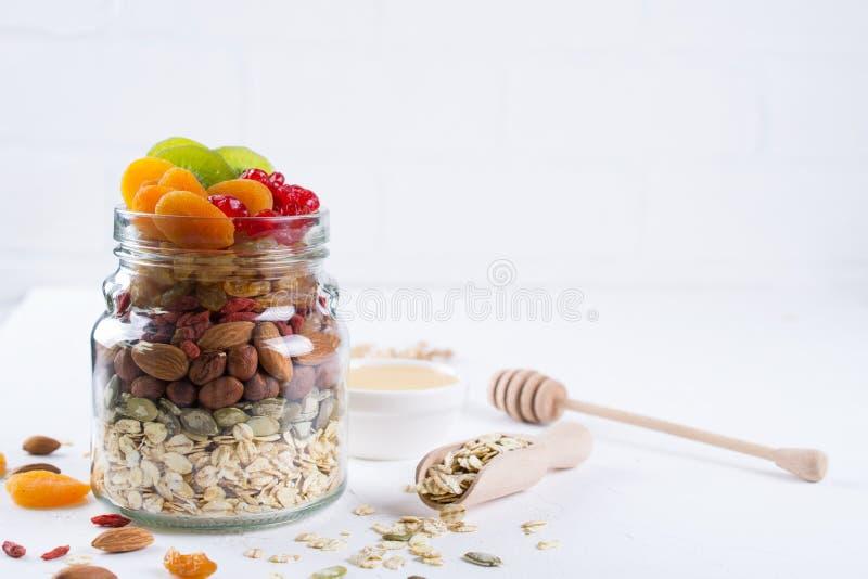 Pot en verre avec des ingrédients pour faire cuire la granola sur le fond blanc Flocons, miel, écrous, fruits secs et graines d'a photographie stock libre de droits