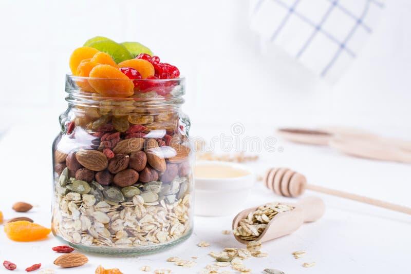 Pot en verre avec des ingrédients pour faire cuire la granola sur le fond blanc Flocons, miel, écrous, fruits secs et graines d'a image libre de droits
