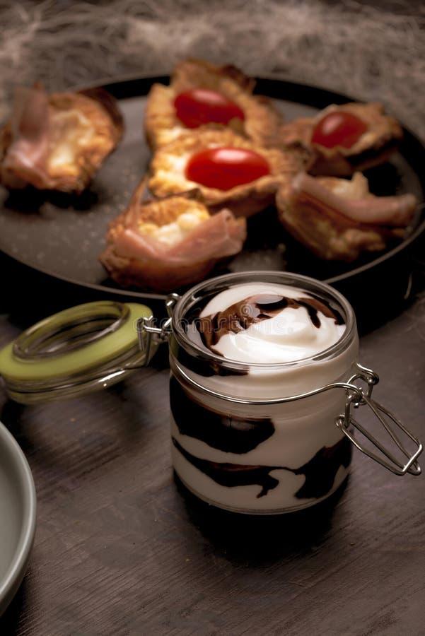 Pot en verre avec la couverture complètement de la sauce blanche et brune sur le conseil en bois foncé images libres de droits