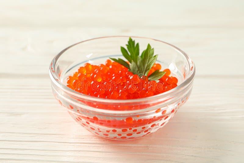 Pot en verre avec le caviar rouge d'isolement sur la table en bois blanche image stock