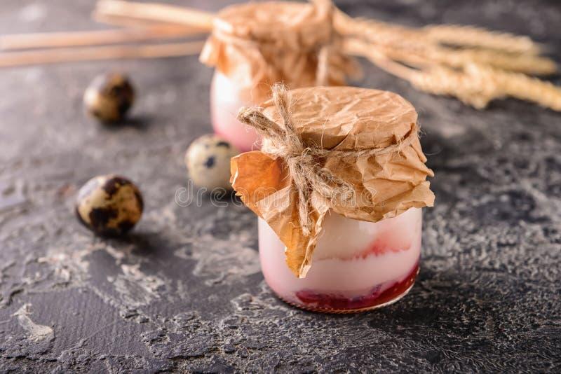 Pot en verre avec le yaourt aux fruits sur la table grunge photographie stock libre de droits