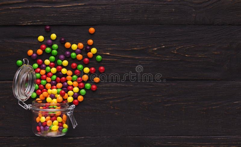 Pot en verre avec les sucreries colorées sur le fond en bois images libres de droits
