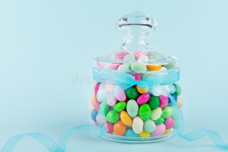 Pot en verre bourré de la sucrerie colorée sur le fond bleu Cadeaux pour l'anniversaire ou les Joyeuses Pâques photo libre de droits
