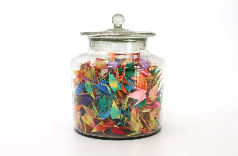 Pot en verre coloré d'oiseaux d'origami en clair photographie stock